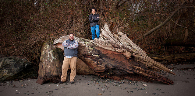 Two men pose against an old fallen tree on a beach.